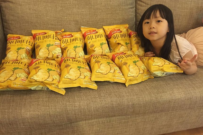 The writer's daughter posing with 12 packs of Honey Butter Chip that became the subject of a treasure hunt during their first housewarming party.