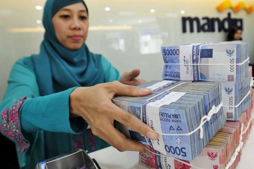 A teller at a Bank Mandiri branch handling Indonesian Rupiah currency during a transaction in Jakarta.