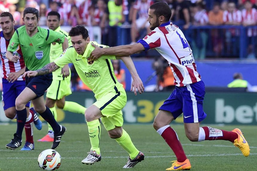 Barcelona's Argentinian forward Lionel Messi (left) vies with Atletico Madrid's midfielder Mario Suarez.