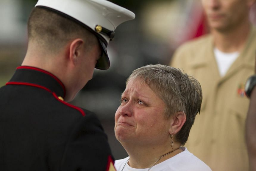 "Cathy Wells, mother of serviceman Squire K. ""Skip"" Wells is given flowers by a marine who served with her son, at her son's vigil."