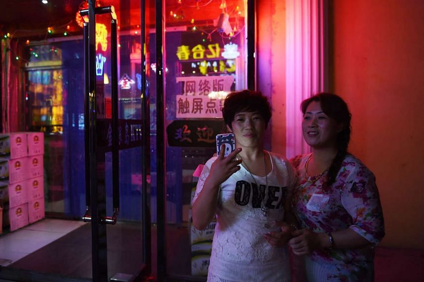 Two women outside a karaoke bar in Hunchun, which shares a border with both Russia and North Korea.