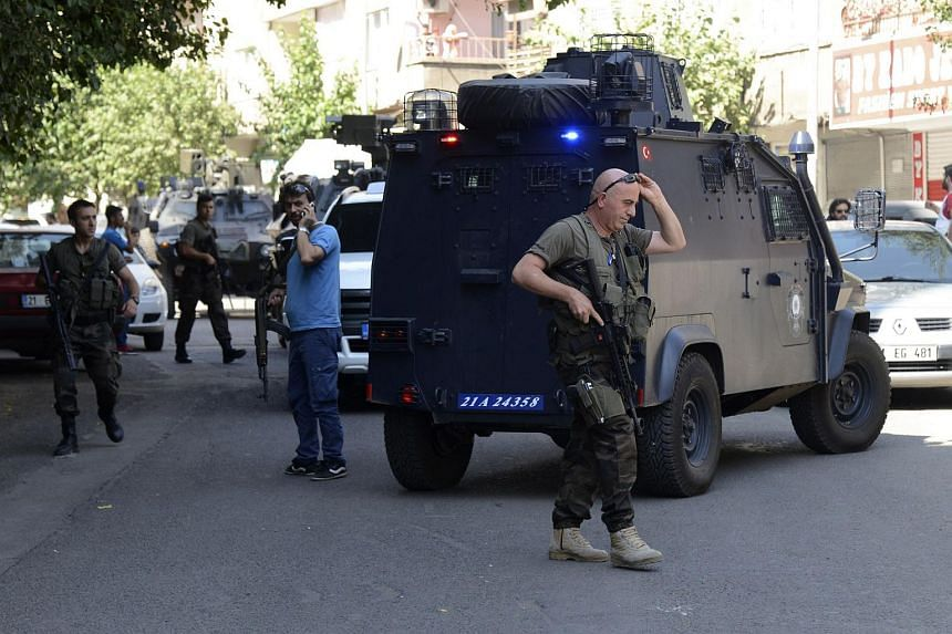 Turkish police officers inspecting the area after an attack against officers left one dead and another wounded, in the centre of Diyarbakir on July 23, 2015.