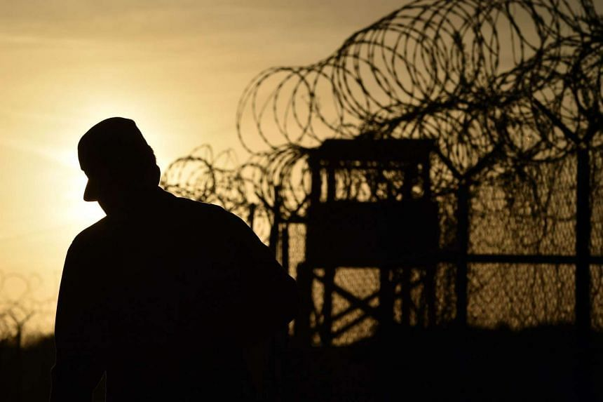 A US soldier walking next to a razor wire-topped fence at the Guantanamo Bay prison in Cuba.