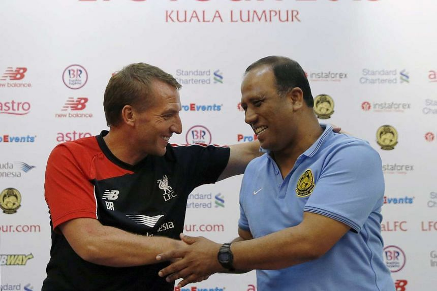 Liverpool manager Brendan Rogers shaking hands with Malaysia XI coach Dollah Saleh (right) at a news conference yesterday, ahead of their friendly match in Kuala Lumpur tomorrow.