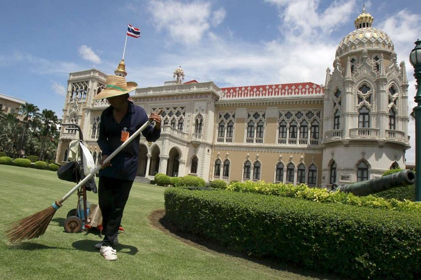 A worker sweeping at the Government House compound in Bangkok, Thailand.