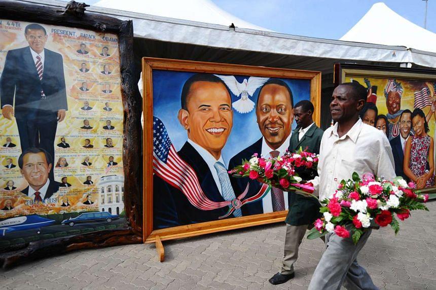 Florists walking past a painting depicting US President Barack Obama and Kenyan President Uhuru Kenyatta in Nairobi.