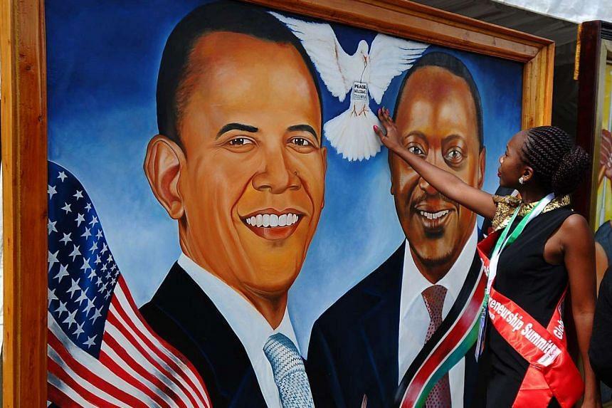 A Kenyan woman touching a painting depicting a dove between US President Barack Obama (left) and Kenyan President Uhuru Kenyatta in Nairobi.
