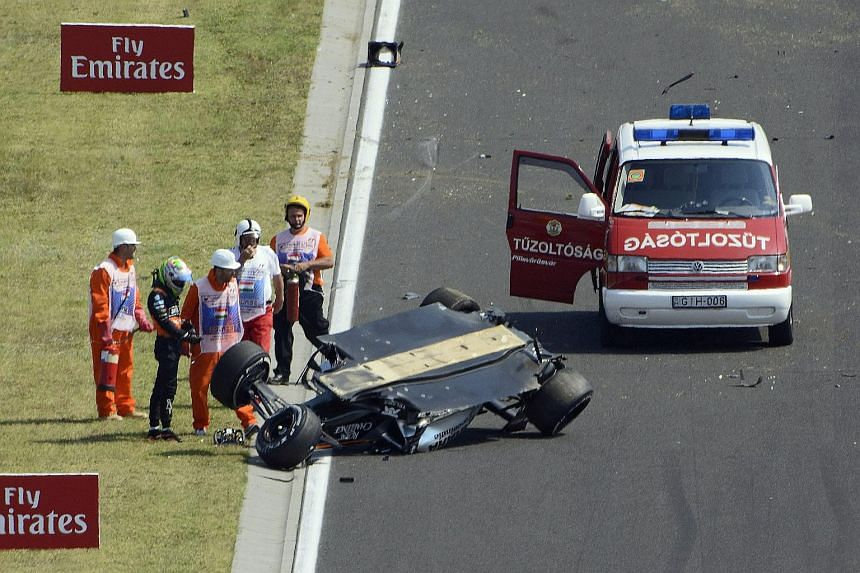 Mexican driver Sergio Perez of Force India standing next to his overturned car during the Hungarian GP's first practice session.
