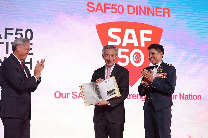 PM Lee launching the SAF50 book as Defence Minister Ng Eng Hen (left) and Chief of Defence Force Ng Chee Meng look on.