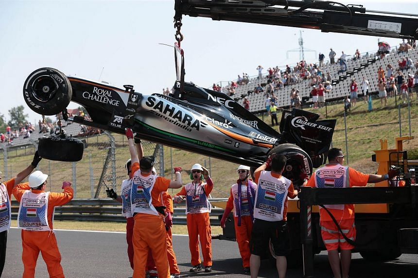 Perez's car being removed by circuit marshals following the crash.