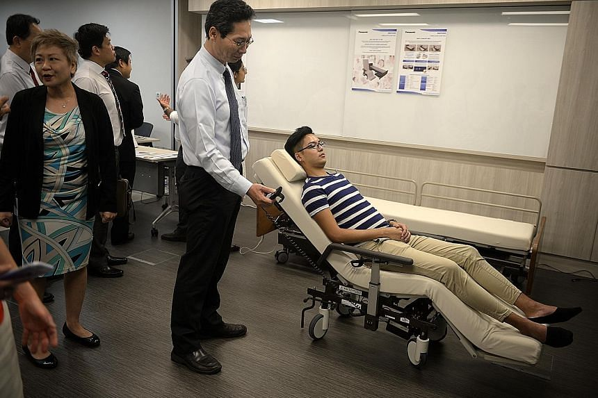 Left: President Tony Tan Keng Yam checking out Nico, a robot that can extract data such as blood pressure or temperature from wearable devices on patients and send the data to a doctor's computer. Nico can also be used in the wards to keep an eye on