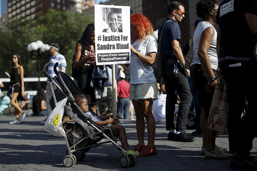 A child holding a poster of Ms Sandra Bland, who died in police custody, during a rally against police violence in New York on Wednesday. Ms Bland, a black woman, was found hanging in her Texas jail cell last week after her arrest following a minor t