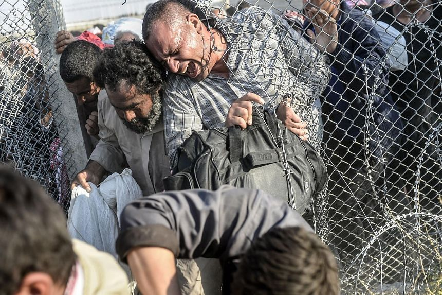 Syrians fleeing the war in their country pushing through an opening in a border fence to enter Turkey. National boundaries are being fortified at a rate not seen since the Sept 11 terror attacks.