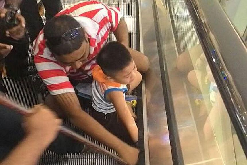 Mr Ng Wei Kang trying to free his son's hand which was stuck in the escalator. The skin on the boy's hand was torn off, but no bones were broken.