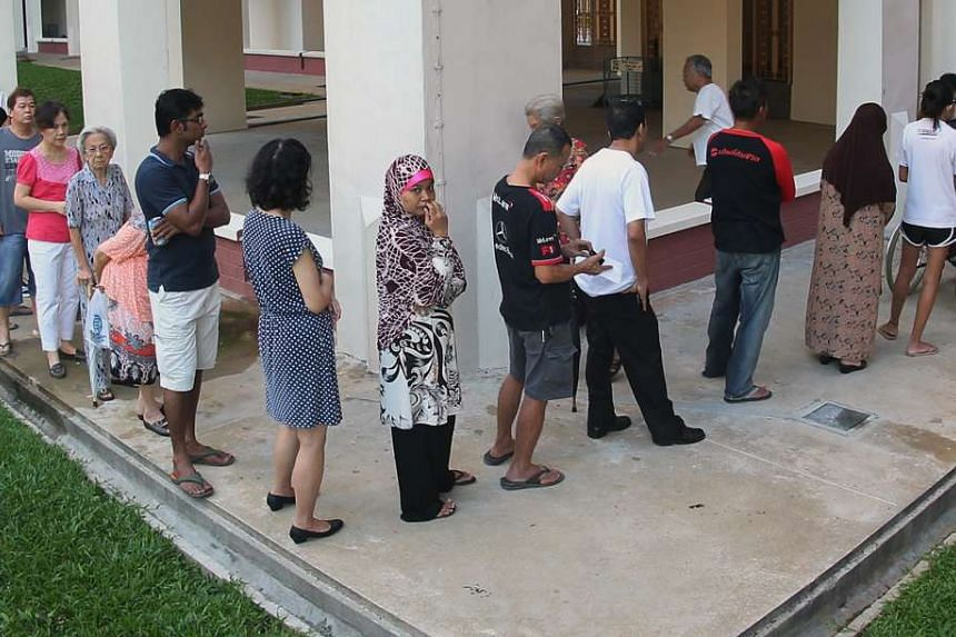 Voters waiting in line at a polling station during polling day on May 7, 2011.