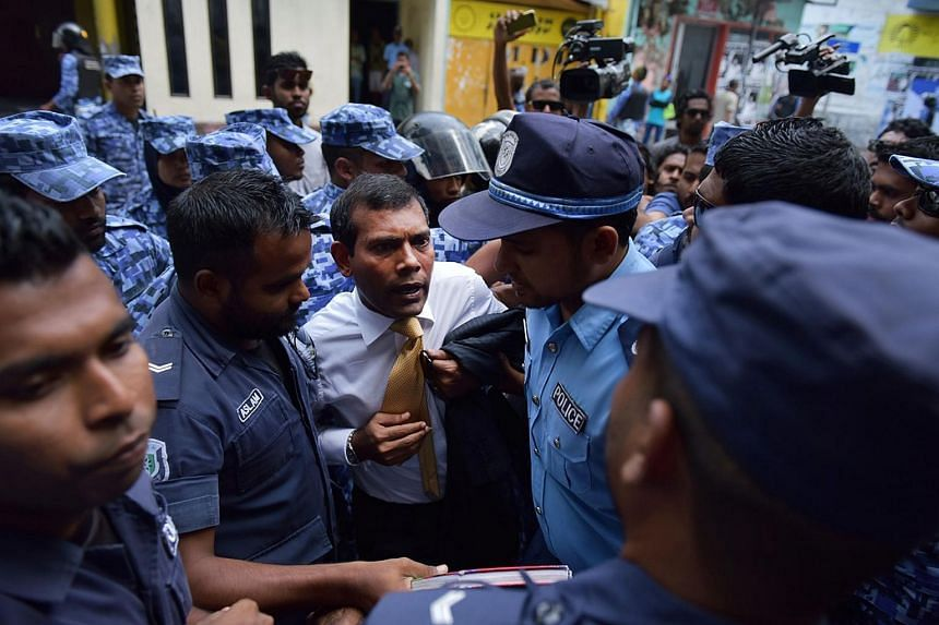 Maldives police try to move former president Mohamed Nasheed (centre) during a scuffle as he arrives at a courthouse in Male on Febuary 23, 2015.