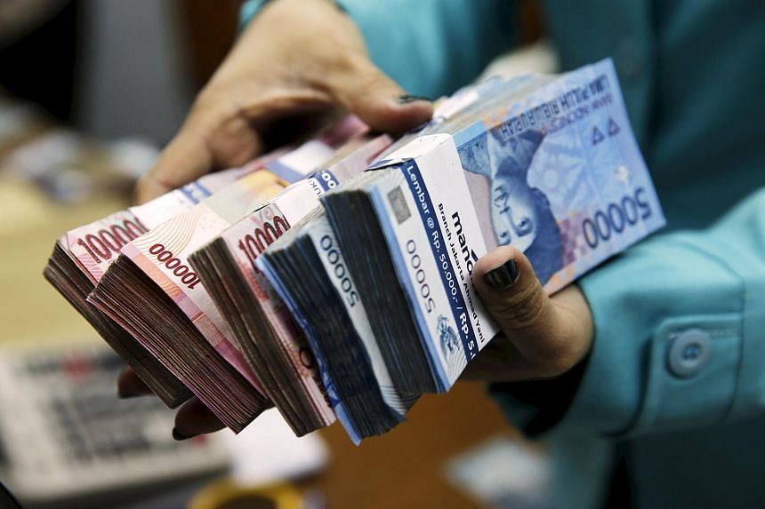 A woman holds Indonesian rupiah notes at money changer in Jakarta, on March 23, 2015.