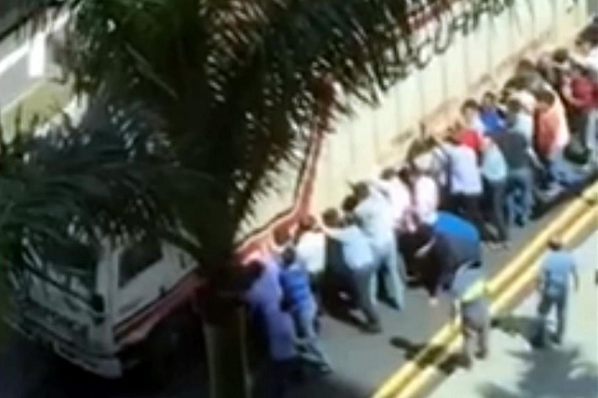 Passers-by help to lift a truck to free a man pinned underneath.