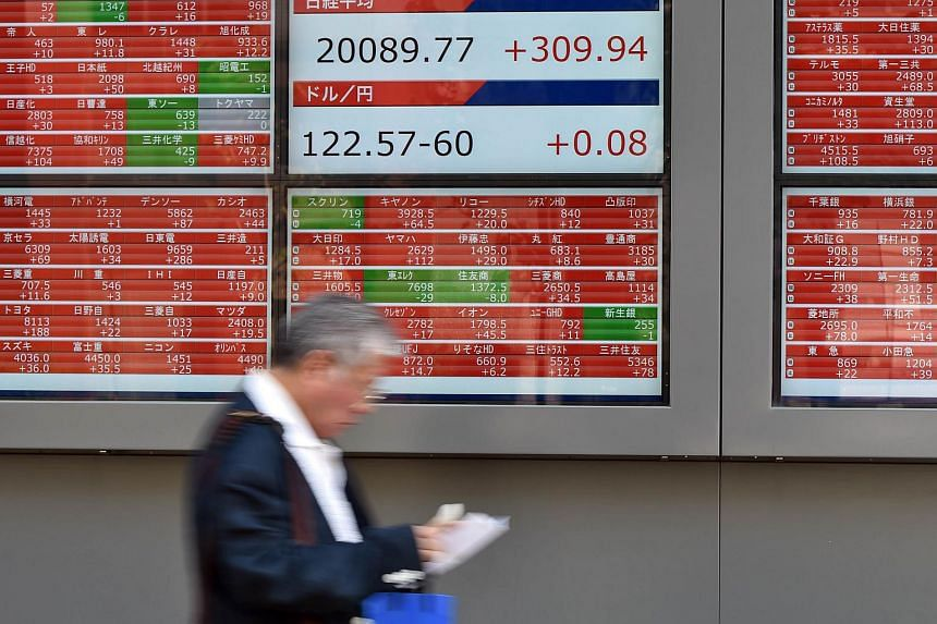 A businessman walks past a board showing the Nikkei 225 index and the yen-US dollar rate in Tokyo on July 13, 2015.