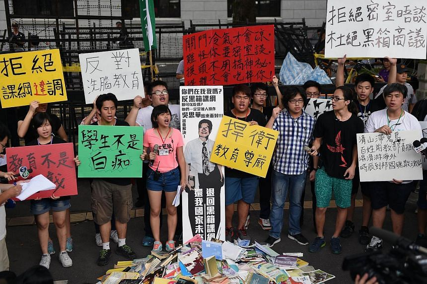 Taiwanese high school students display placards against the revision of history text books during a demonstration in front of the education ministry in Taipei on July 22, 2015.