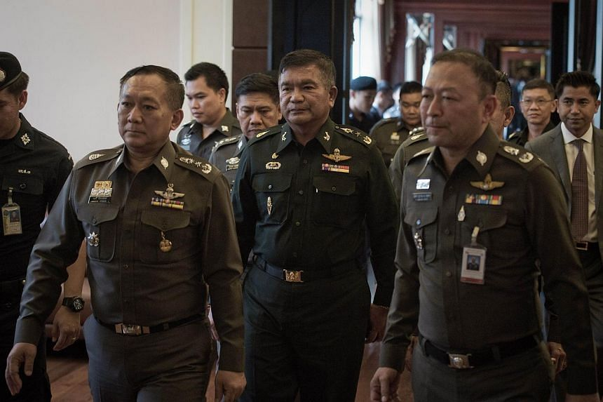 Thai Army Lieutenant General Manas Kongpan (centre) is surrounded by police officers as he turns himself in at the police headquarters in Bangkok on June 3, 2015.