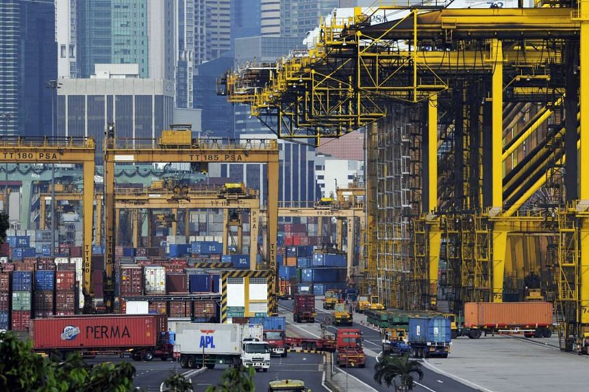 Shipping containers are moved and stacked at the port of Singapore.