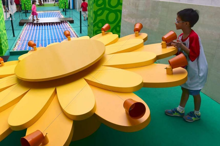 At the National Museum of Singapore's Masak Masak exhibition, an installation encourages children to match the correct strings to communicate through tin-can telephones.