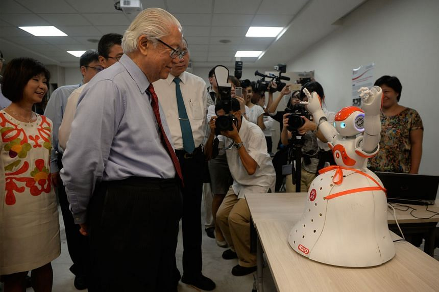 President Tony Tan Keng Yam checking out Nico, a robot that can extract data such as blood pressure or temperature from wearable devices on patients and send the data to a doctor's computer. Nico can also be used in the wards to keep an eye on patien