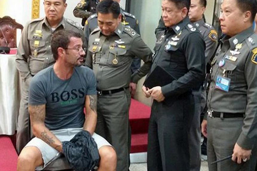 Swiss national Xavier Justo (seated) surrounded by Thai police officers.