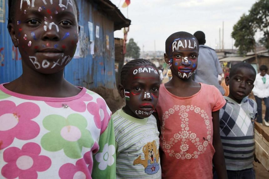 """Children with painted faces reading """"Obama is coming""""."""