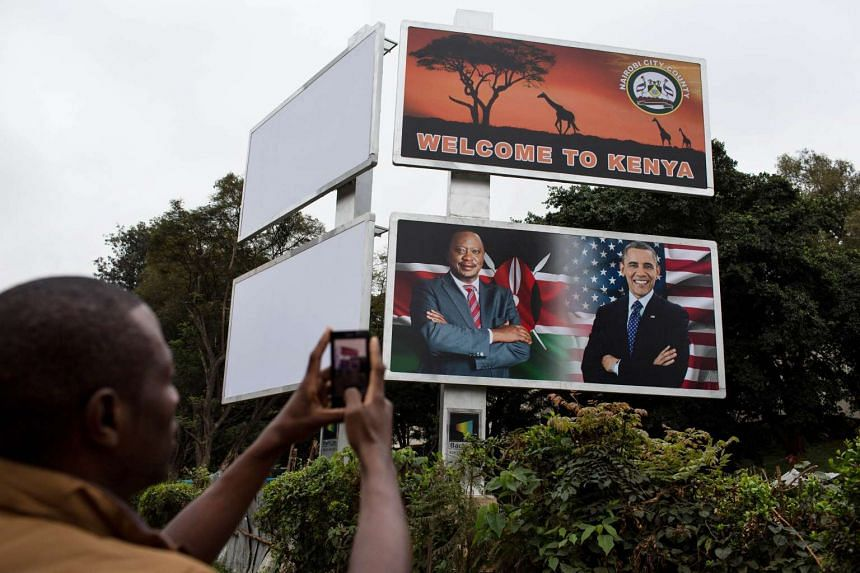 A man takes a picture of a huge billboard with US President Obama and Kenyan President Uhuru Kenyatt.