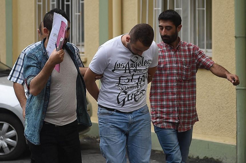 Turkish plainclothes police officers with a suspected ISIS member at a hospital yesterday in Istanbul. Hundreds of suspected militants were arrested, the government said.