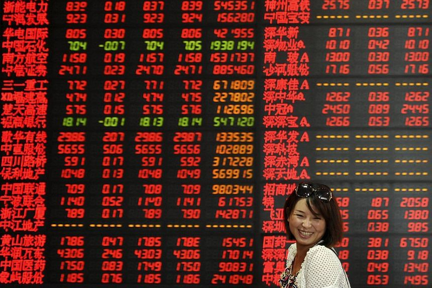 An investor walks past an electronic board showing stock information at a brokerage house in Fuyang, Anhui province, China.
