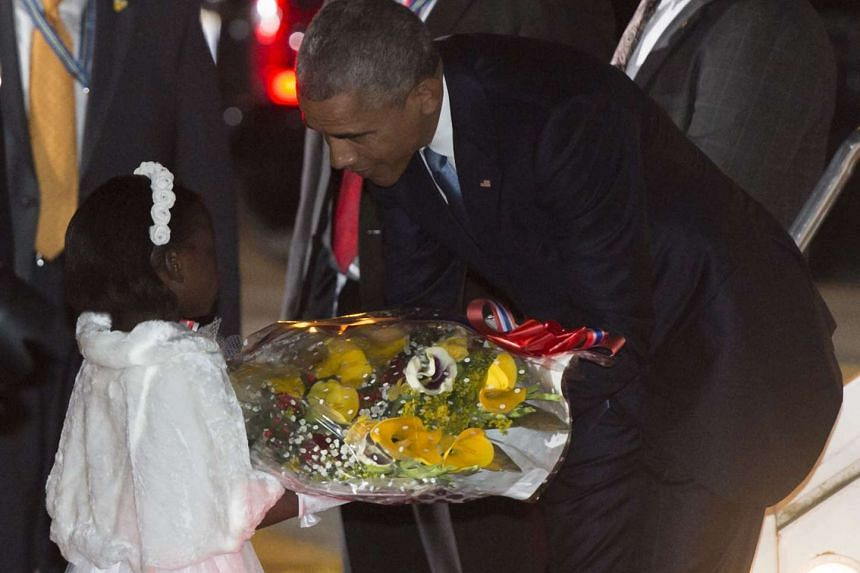 Obama receives flowers from Joan Wamaitha, eight, upon his arrival.