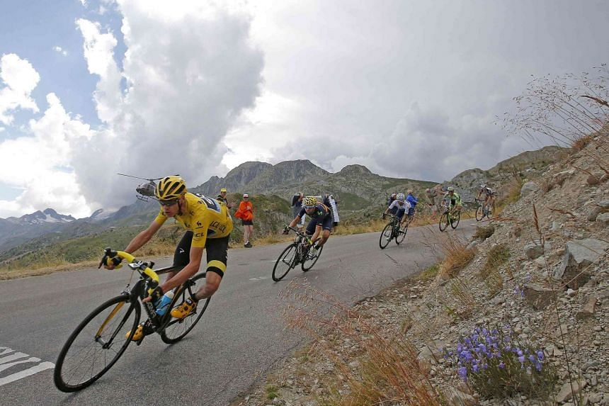 Froome, in the overall race leader's yellow jersey, speeds downhill in the Glandon pass during the 19th stage of the Tour de France.
