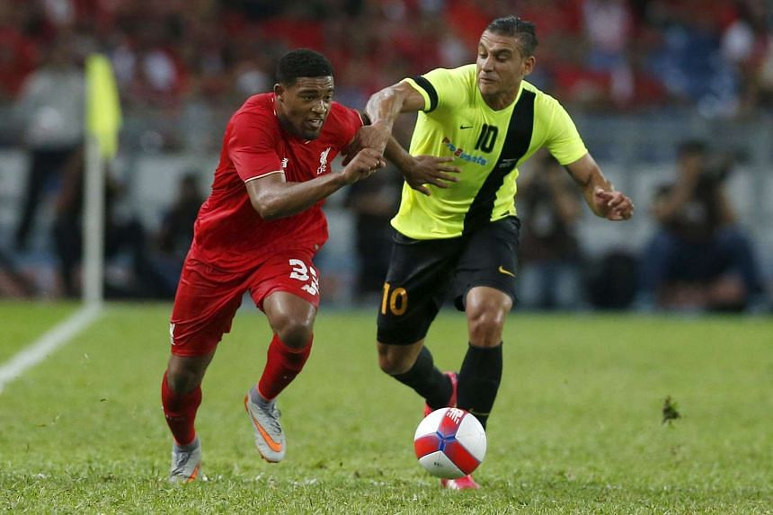 Liverpool's Jordon Ibe (left) fights for the ball with Malaysia's Charles Souza Chad.