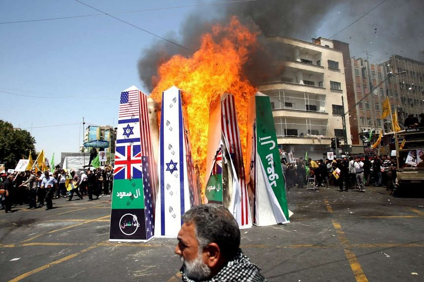 Iranian demonstrators burn symbolic structures depicting the flags of the US, Britain, and Israel during a rally marking al-Quds (Jerusalem) Day in Teheran July 10, 2015.