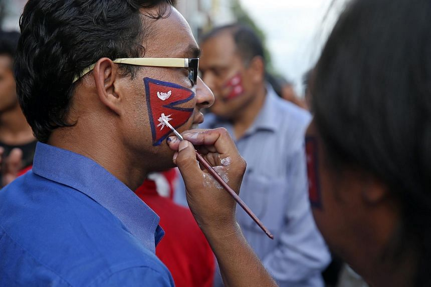 Locals painting their faces with the Nepal flag at a public rally calling for tourists to return on June 23.