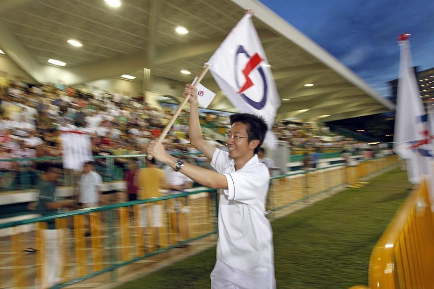 A People's Action Party supporter carrying the party flag at its rally for East Coast GRC at Bedok Stadium on May 1, 2011.