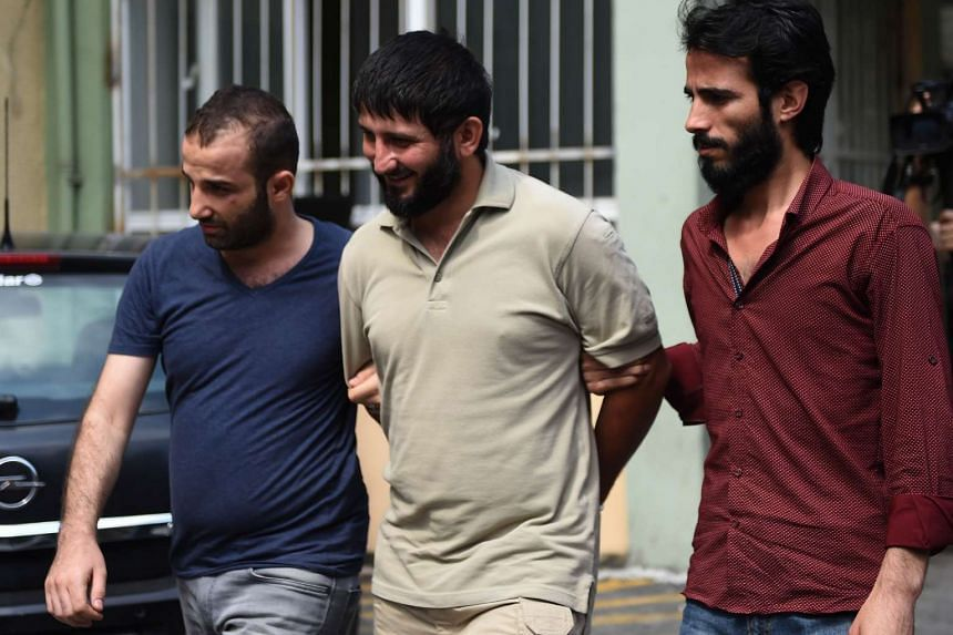 Turkish plain-clothes police officers escort a suspected ISIS militant at a hospital for a medical check-up on July 24, 2015 in Istanbul.
