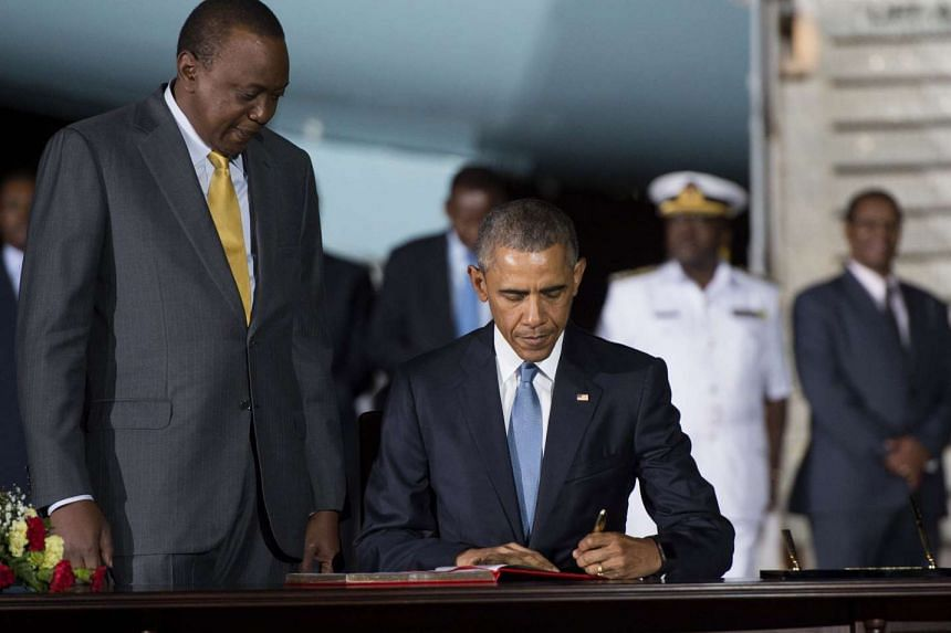 Obama signs a guestbook alongside Kenyan President Uhuru Kenyatta upon his arrival in Kenya.