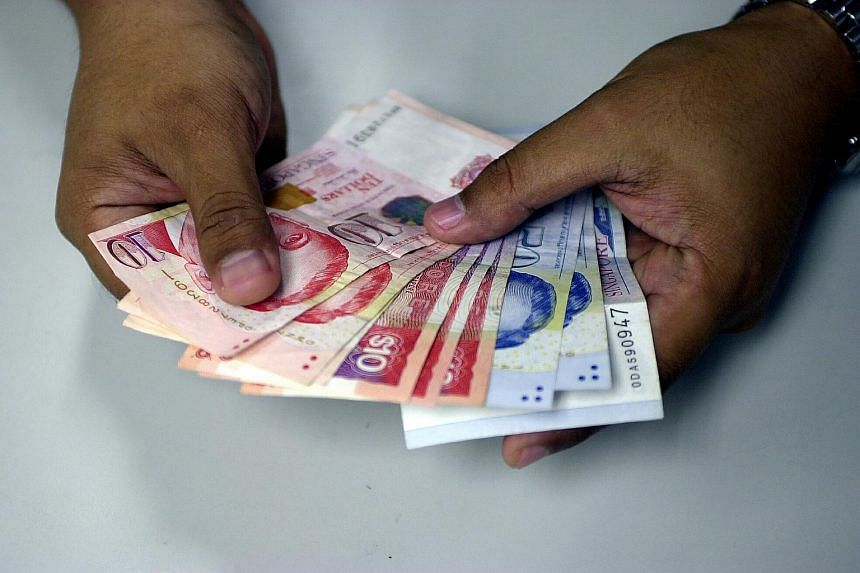 Posed photo of hand holding Singapore dollar notes.