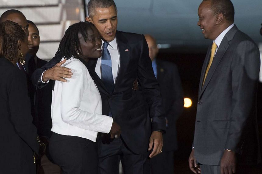 Obama (centre) greets his half-sister Auma Obama (left) alongside Kenyan President Uhuru Kenyatta.