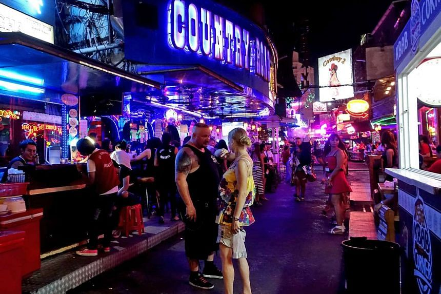 Revellers yesterday visiting Soi Cowboy, a small lane filled with pubs popular with tourists in Bangkok. Restaurant and bar owners fear the restrictions will devastate entertainment areas that make the Thai capital a tourist magnet and big money spinner.