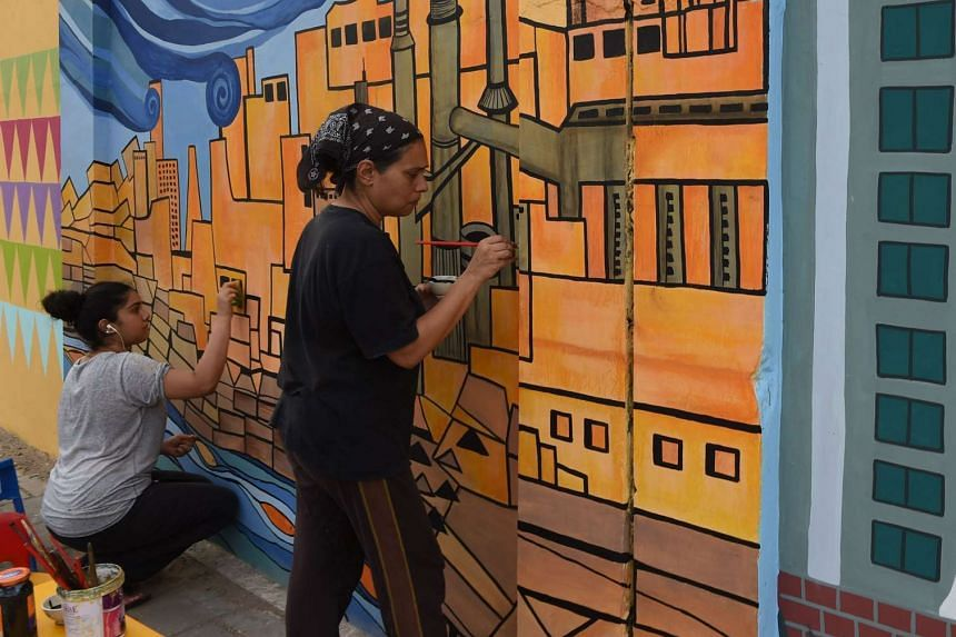 Art teacher Norayya Shaikh Nabi (right) and her daughter, Gaiti Ara, adding finishing touches to a wall mural in Karachi on May 31. A group of volunteers hopes to bring happiness and pride to the city.