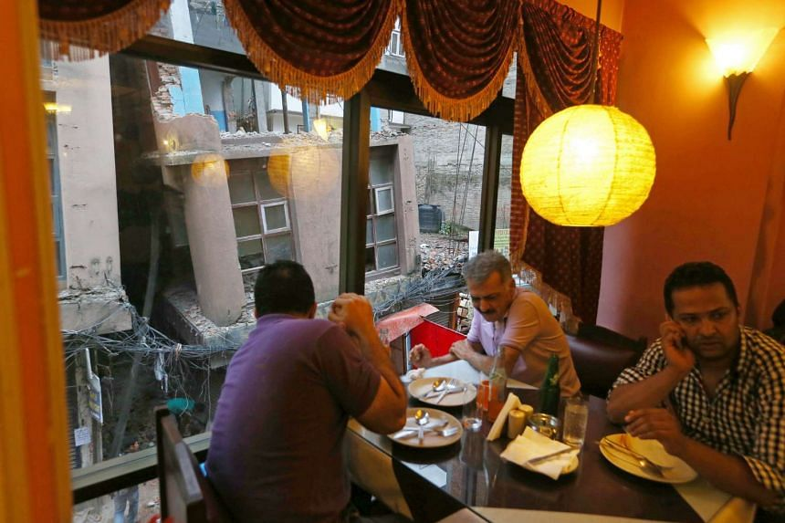 Diners in a Kathmandu restaurant which overlooks a toppled building.