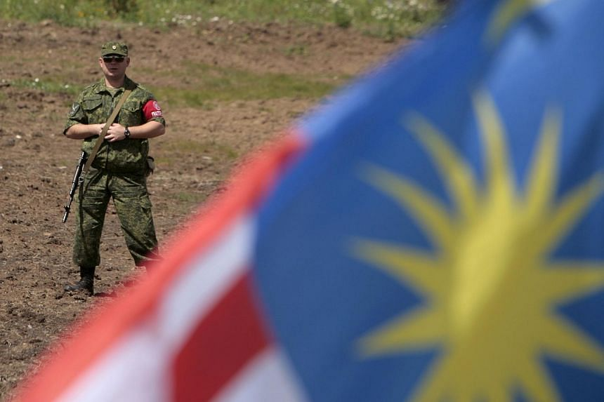 A member of the self proclaimed Donetsk People's Republic forces stands guard during a commemoration ceremony at the site of the Malaysia Airlines flight MH17 plane crash near the village of Hrabove in Donetsk region, Ukraine, July 17, 2015.