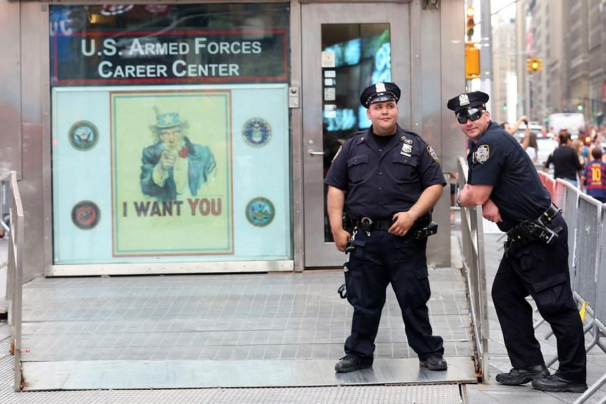 New York City Police Officers stand outside a US Armed Forces Recruiting Center in Times Square in New York, USA.