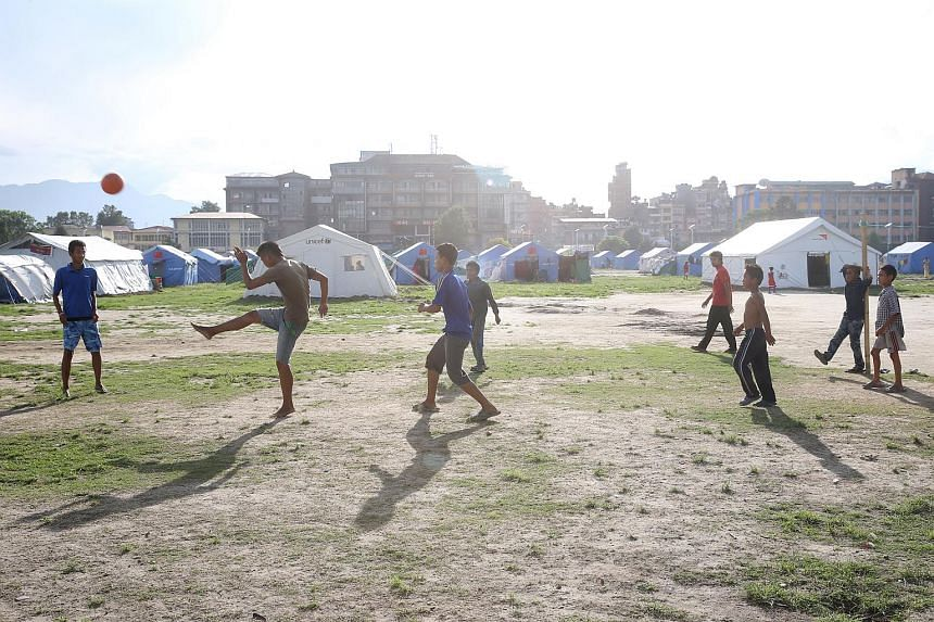 Boys playing football in Tundikhel, a vast compound in Kathmandu where temporary shelters have been set up for victims of the April 25 earthquake.
