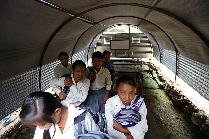 Students from Shree Bageswari Secondary School in Makwanpur District, about three hours' drive from Kathmandu, taking a look inside a temporary classroom set up after the April 25 earthquake.